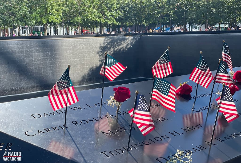 9/11 Memorial with many flags on the edge on one of the pools.